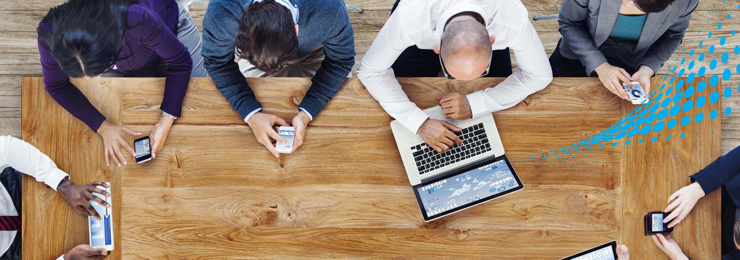Mesa com homens e mulheres usando celulares e computadores conectados no wifi