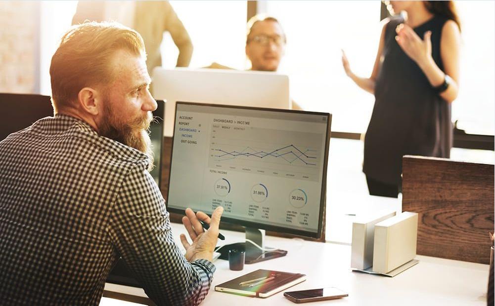 Homem no escritório conversando com pessoas em sua volta e mostrando os dados de gerenciamento na tela do seu computador